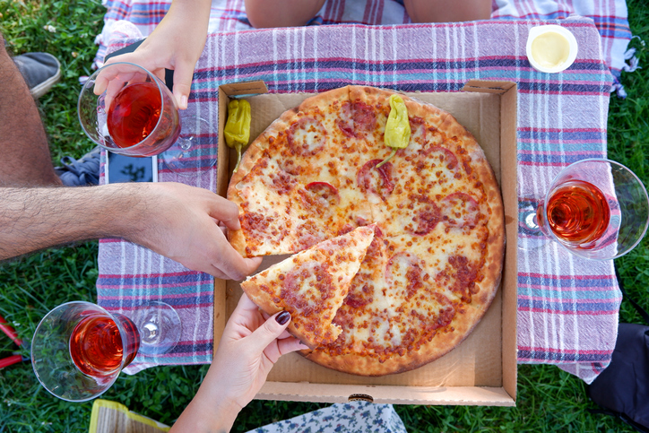 Young parents with their child making picnic with pizza and rose wine on city park outdoor