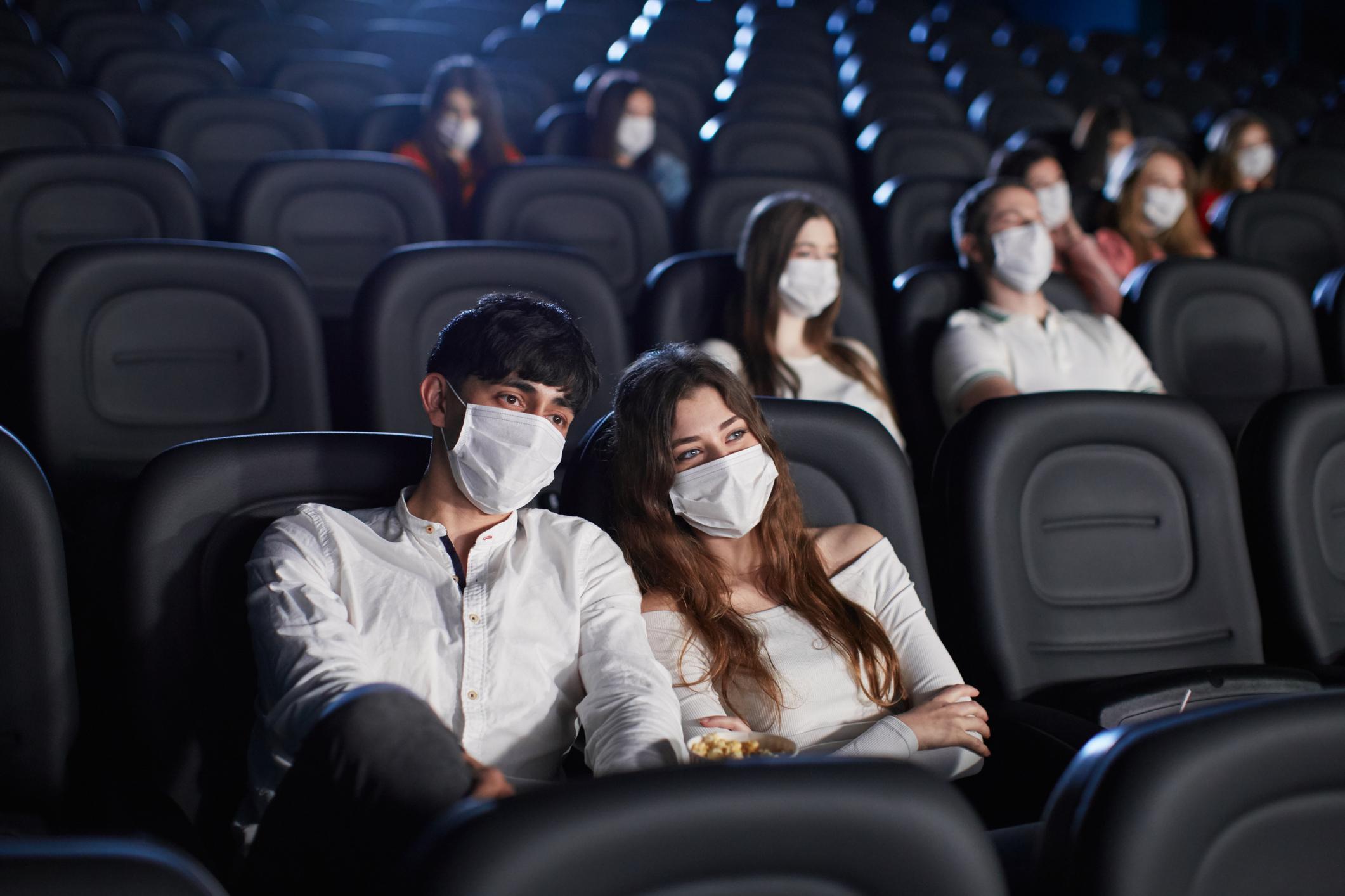 Audience wearing face masks enjoying time in cinema.