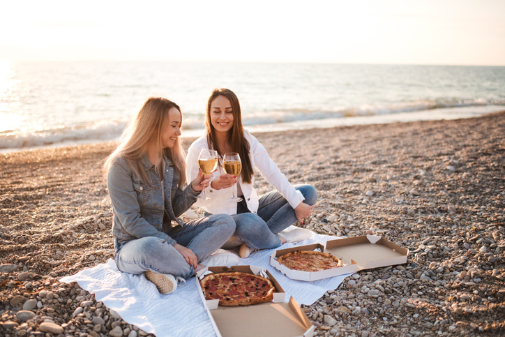 Two young adult girls having picnic outdoors. Love couple together.