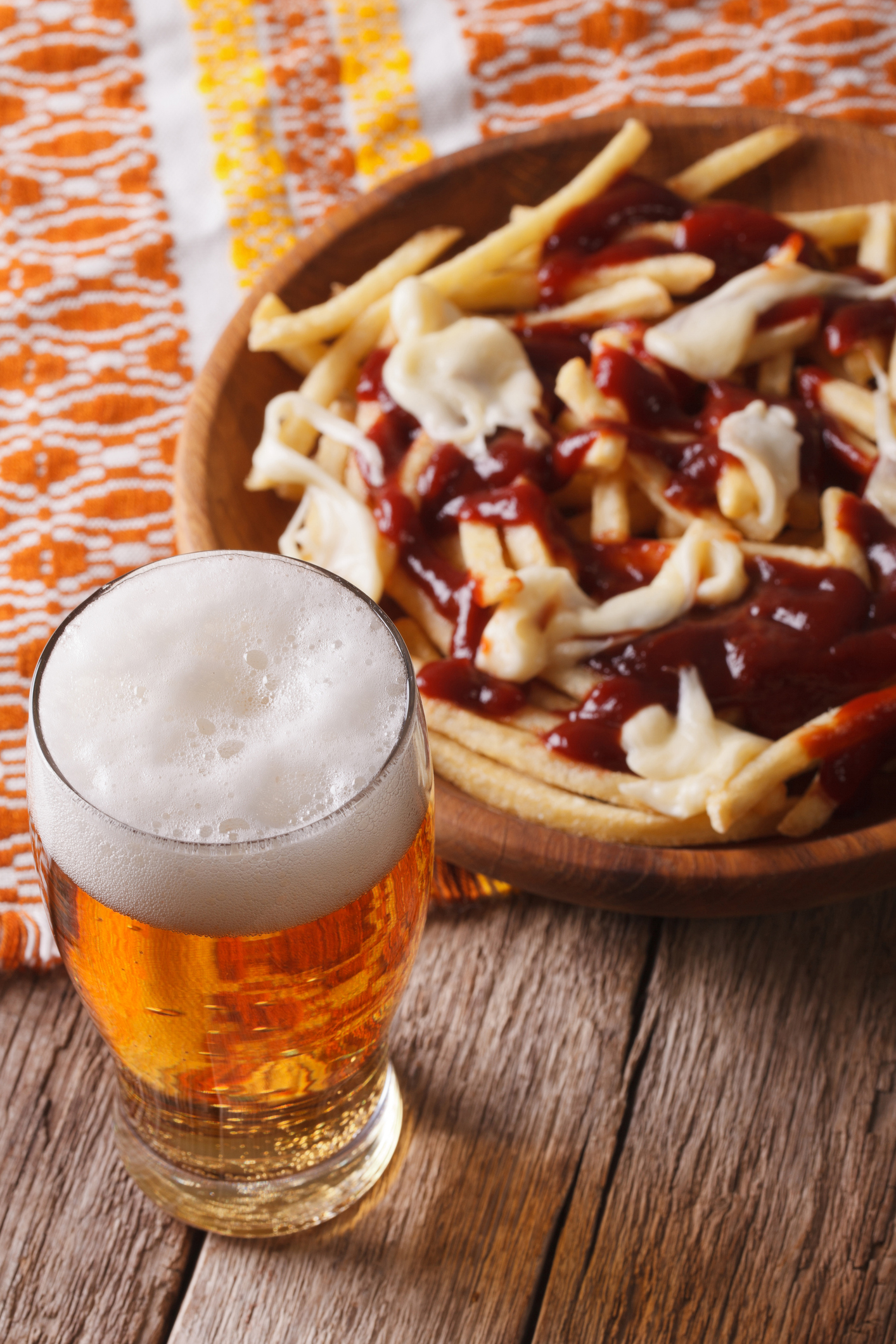 Canadian food: beer and fries with sauce close-up. Vertical