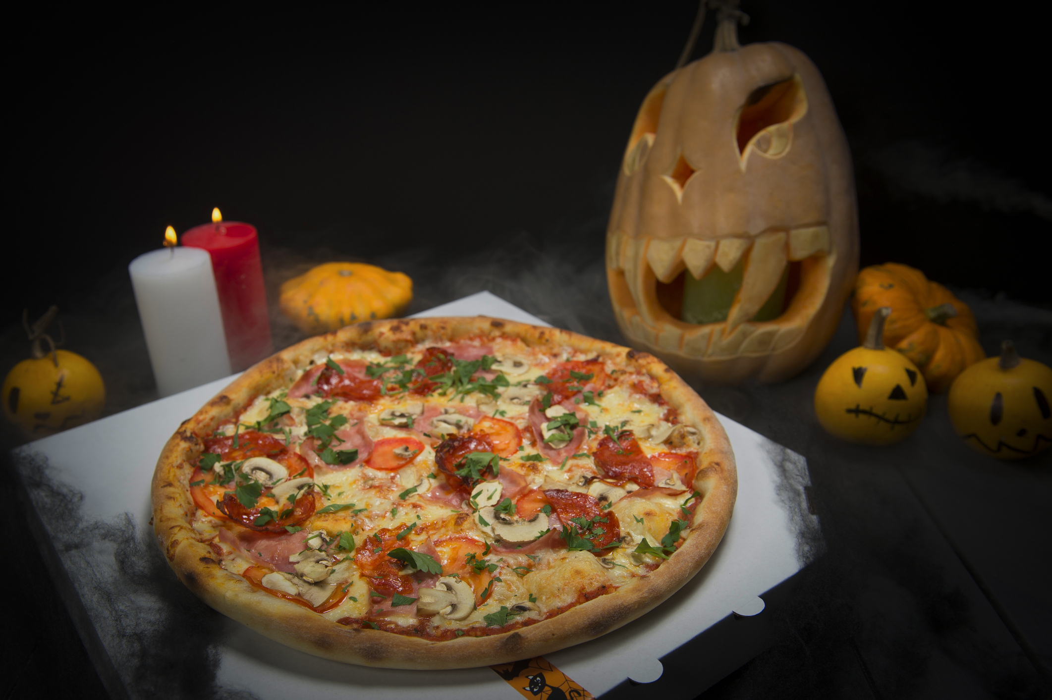 meat pizza near Halloween decoration: Scary pumpkins with painted faces, Lights of burning candles In horror smoke.