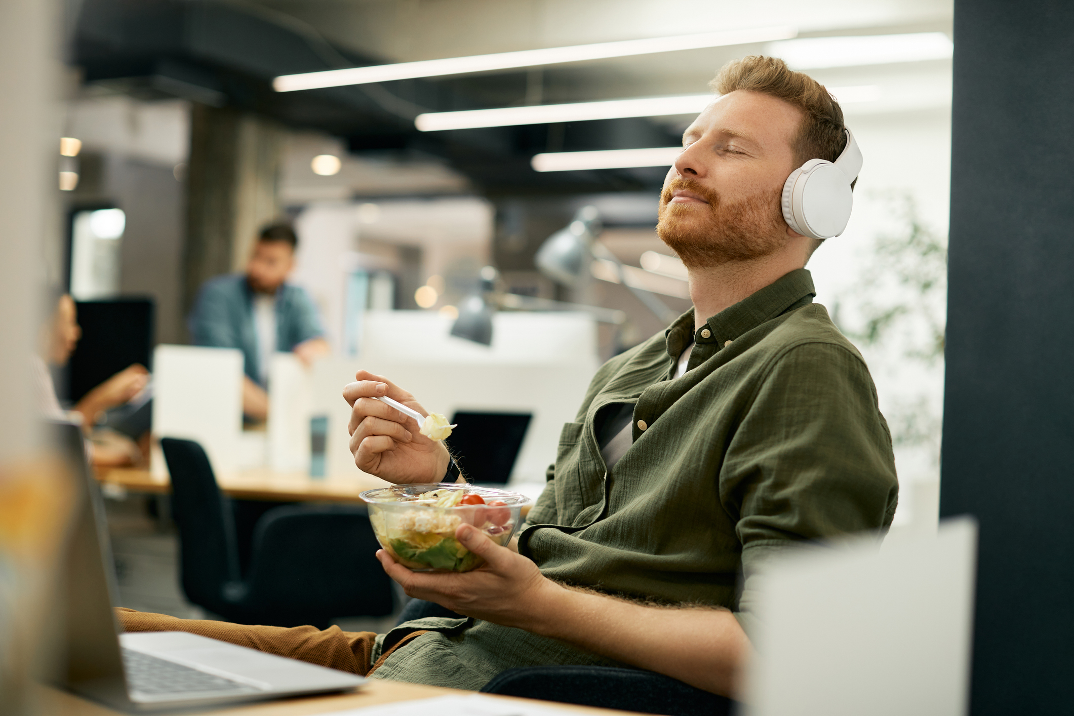 Relaxed businessman enjoying in music over headphones on lunch break in the office.
